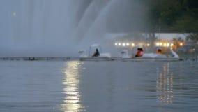 Os povos borrados estão montando o barco do pato no parque público video estoque