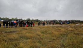 Os povos com guarda-chuvas sob uma chuva esperam o veículo através dos campos Fotos de Stock Royalty Free