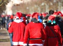 Os povos com roupa vermelha de Santa Claus correm durante ostentar mesmo Foto de Stock
