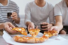 Os povos comem o fast food Mãos dos amigos que tomam fatias de pizza imagens de stock royalty free
