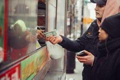 Os povos compram o alimento da rua em New York City e pagam-no no dinheiro ao vendedor fotos de stock royalty free