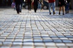 Os povos cruzam a estrada em um cruzamento pedestre no pavimento mim imagem de stock
