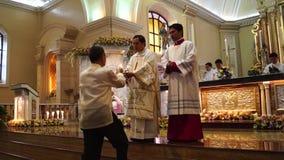 Os povos da configuração trazem ofertas ao altar durante a celebração maciça filme