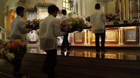 Os povos da configuração trazem ofertas da flor ao altar durante a celebração maciça video estoque