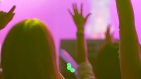 Os povos da multidão com smartphone fazem a foto em fundo unfocused do evento da noite em iluminar o holofote filme