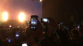 Os povos da multidão guardam o smartphone em suas mãos O fã do homem toma o telefone celular da imagem video estoque