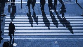 Os povos da silhueta andam na faixa de travessia pedestre na junção Imagem de Stock