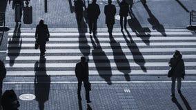 Os povos da silhueta andam na faixa de travessia pedestre na junção fotografia de stock royalty free