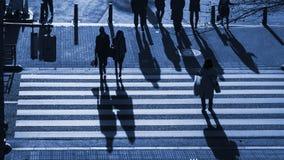 Os povos da silhueta andam na faixa de travessia pedestre na junção s Fotos de Stock
