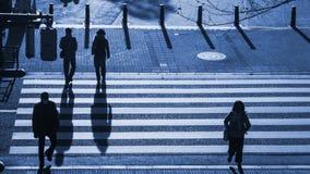 Os povos da silhueta andam na faixa de travessia pedestre na junção s Fotos de Stock Royalty Free