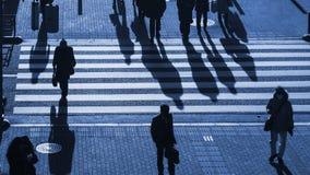 Os povos da silhueta andam na faixa de travessia pedestre na junção s Imagem de Stock