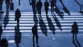 Os povos da silhueta andam na faixa de travessia pedestre na junção s Fotografia de Stock Royalty Free