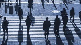 Os povos da silhueta andam na faixa de travessia pedestre na junção s Foto de Stock