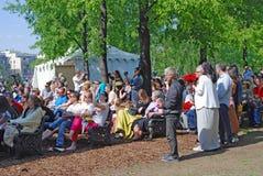 Os povos de idades diferentes sentam-se e estão-se em um parque Fotos de Stock