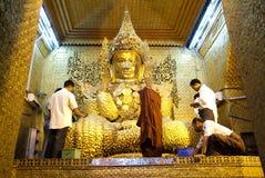 Os povos de Myanmar veneraram a estátua da Buda com o papel dourado Fotos de Stock Royalty Free