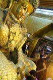 Os povos de Myanmar veneraram a estátua da Buda com o papel dourado Fotografia de Stock