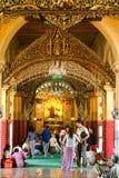 Os povos de Myanmar veneraram a estátua da Buda com o papel dourado Imagem de Stock Royalty Free