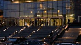 Os povos deixam o centro de negócios, após o trabalho, na noite O movimento dos carros e dos táxis vídeos de arquivo