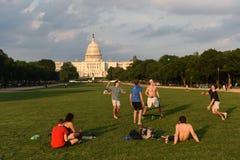 Os povos descansam e jogam a bola na alameda nacional com o Capitólio do Estados Unidos no fundo imagens de stock