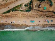 Os povos descansam na praia selvagem com suas famílias imagem de stock