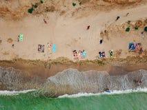 Os povos descansam na praia selvagem com suas famílias fotografia de stock royalty free