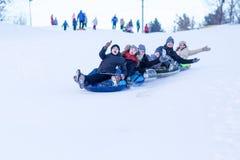 Os povos deslizam para baixo do monte da neve fotografia de stock royalty free