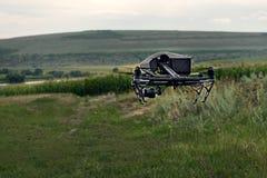 Os povos do conceito e a agricultura - zangão preto com voo da câmara digital no céu sobre o campo no por do sol imagem de stock