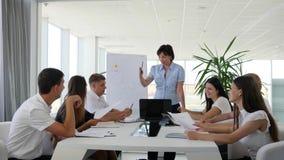 Os povos do escritório com originais nas mãos sentam-se na tabela grande e falam-se com o diretor sobre o negócio de negócio na s video estoque