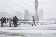Os povos do mau tempo dos povos das horas de ponta v?o trabalhar a realidade pesada do blizzard da neve da neve da vida imagem de stock