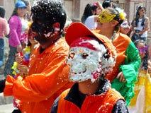 Os povos e os dançarinos estão pulverizando a espuma em todos na parada tradicional para o carnaval em Cuenca fotografia de stock royalty free
