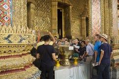 Os povos e o viajante juntam-se a polvilhar tailandês dos lótus do uso da cerimônia Imagem de Stock Royalty Free