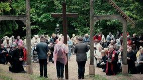 Os povos e os padres religiosos ajoelham-se para baixo em joelhos e rezam-se na frente da cruz vídeos de arquivo