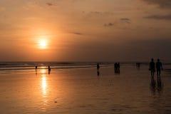 Os povos em Kuta encalham, Seminyak no por do sol em Bali, Indonésia Imagens de Stock