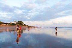 Os povos em Kuta encalham, Seminyak, uma de atrações populares em Bali, Indonésia Foto de Stock