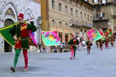 Os povos em trajes tradicionais com bandeiras e cilindros estão indo em Praça del Campo no dia de Contrada imagem de stock royalty free