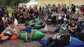 Os povos encontram-se em beanbags na terra no parque Festival do verão Ame pares audiências video estoque