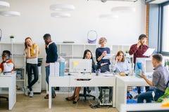 Os povos energéticos do escritório estão usando telefones celulares no trabalho imagem de stock royalty free