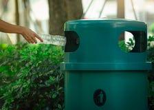 Os povos entregam a garrafa de água vazia de jogo na reciclagem no parque O pl?stico verde recicl o escaninho Garrafa do descarte foto de stock