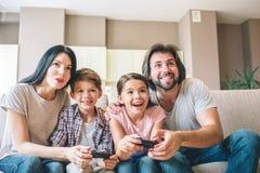 Os povos entusiasmado estão sentando-se junto no sofá Ajuda dos pais para jogar suas crianças As crianças são surpreendidas olhe  fotos de stock