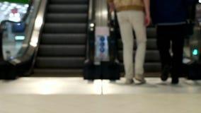 Os povos escalam e montam em uma escada rolante dentro de um shopping, escadaria borrada, movente video estoque