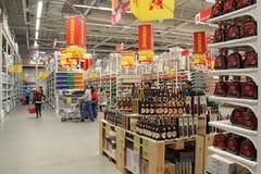 Os povos escolhem da variedade larga de bebidas alcoólicas em prateleiras do supermercado foto de stock
