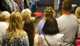 Os povos esperam com bagagem no aeroporto, vista da parte traseira blurry fotografia de stock royalty free