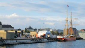 Os povos estão dando uma volta em um cais em um porto de Copenhaga na noite ensolarada, barco são amarrados filme