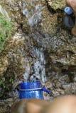 Os povos estão rearquivando suas garrafas de água fora do córrego da montanha Fotos de Stock