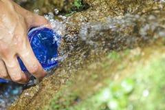 Os povos estão rearquivando suas garrafas de água fora do córrego da montanha Fotografia de Stock Royalty Free