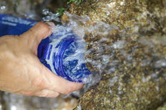 Os povos estão rearquivando suas garrafas de água fora do córrego da montanha Foto de Stock Royalty Free