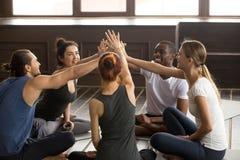 Os povos felizes diversos do iogue alcançam as mãos para dar a elevação cinco foto de stock