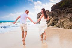 Os povos felizes felizes vestiram-se no corredor branco na praia Fotografia de Stock Royalty Free