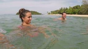 Os povos felizes que nadam na câmera da ação do mar molham o pov do grupo novo dos amigos junto na praia filme