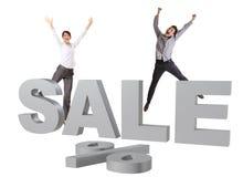 Os povos felizes que saltam atrás da VENDA de prata grande assinam Fotografia de Stock Royalty Free